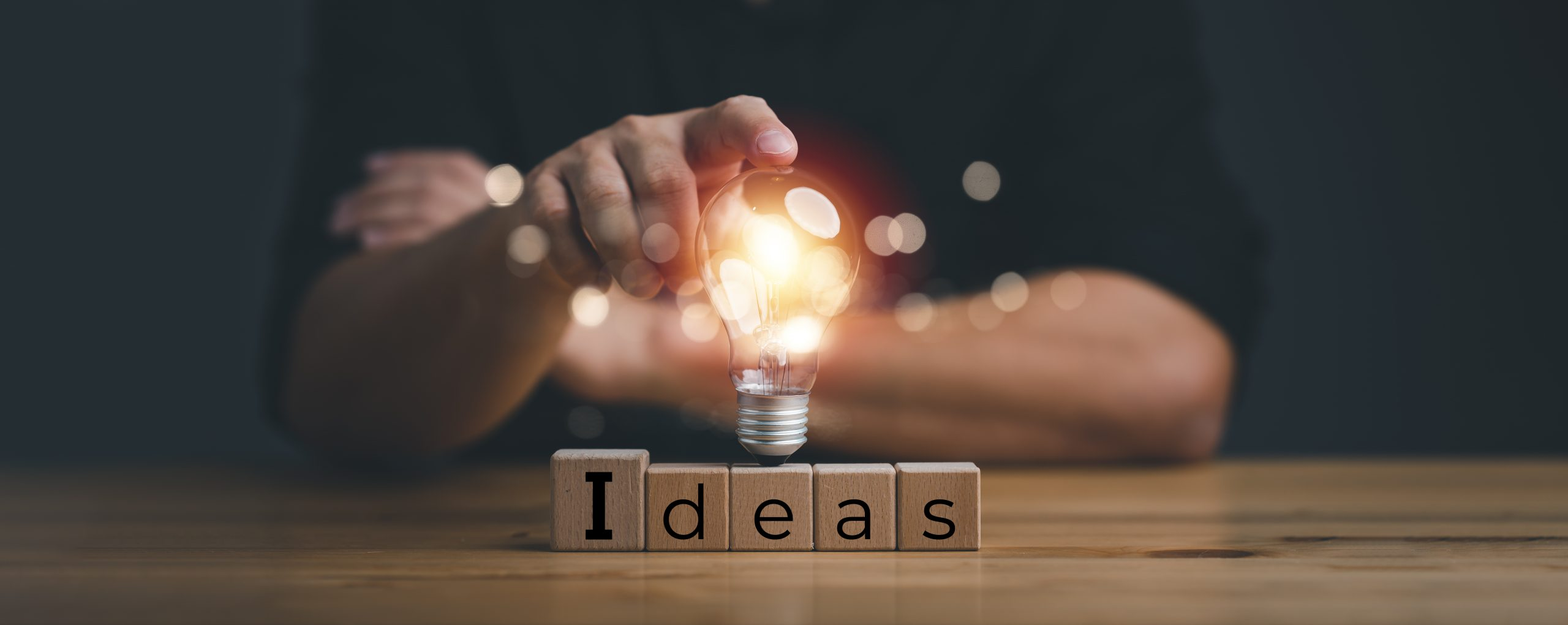 hand touching on light bulb on wood block with Word Ideas, new idea concept with innovation and inspiration, innovative technology in science and communication concept.